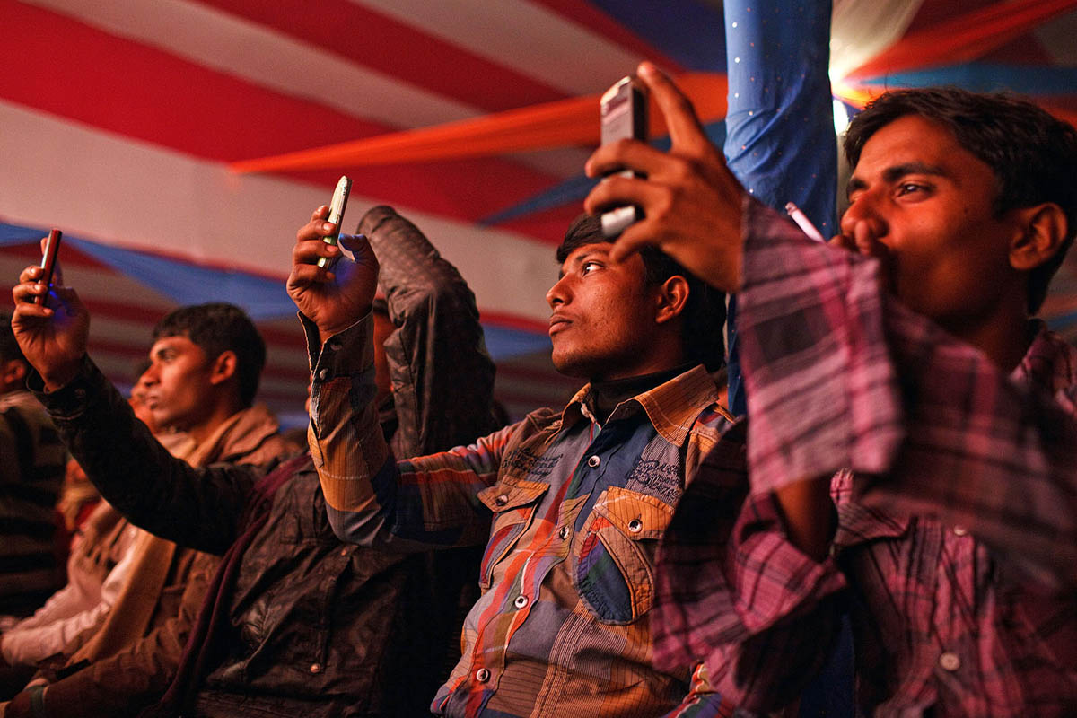 Young Indian men film on their mobile phones girls dancing on the stage inside on of the theatres at Sonepur Mela