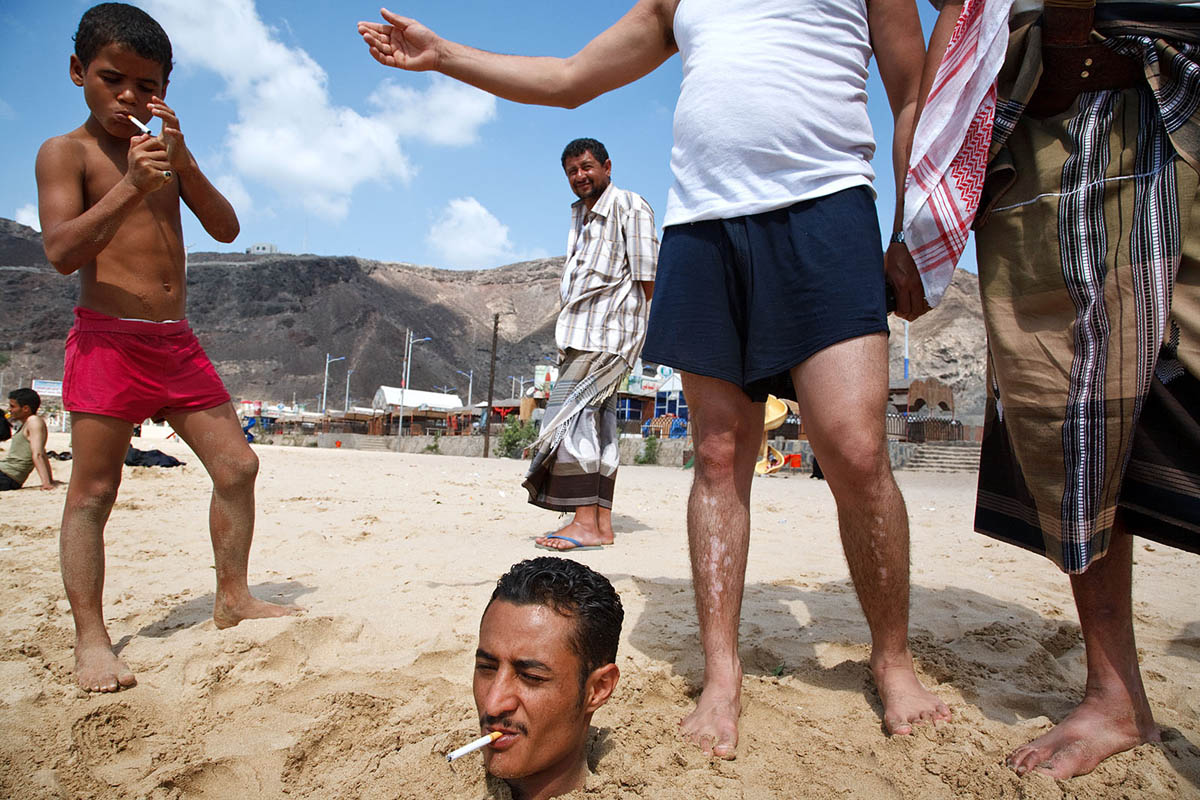 A man buried in the sand on the beach in Aden, Yemen.